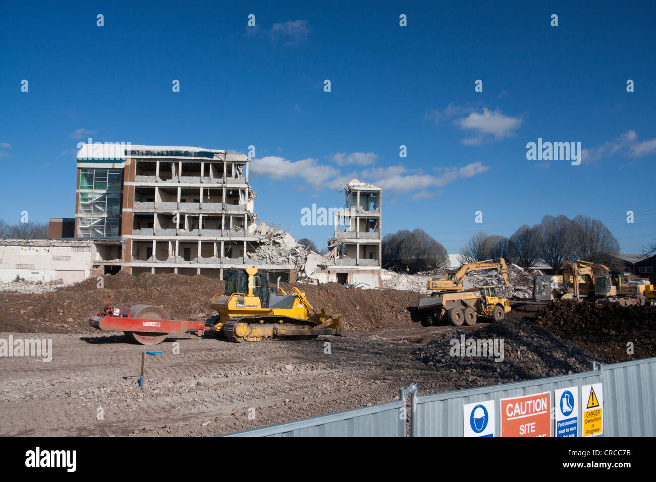 Partly demolished building with mechanical digger clearing away rubble in foreground Cardiff Wales UK - Stock Image