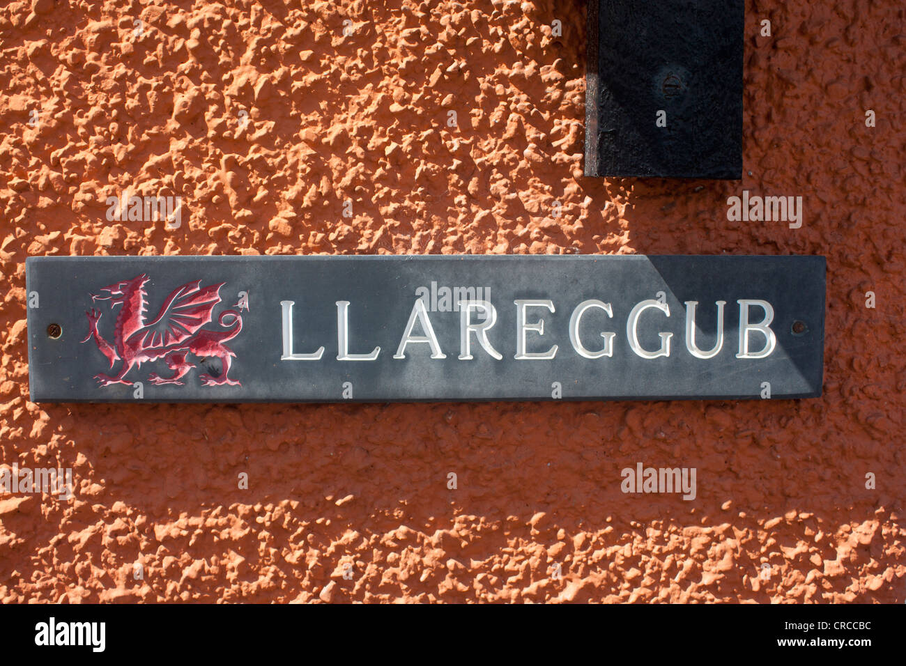 'Llareggub' slate name plate with red Welsh dragon on exterior of house in New Quay Ceredigion Cardigan - Stock Image
