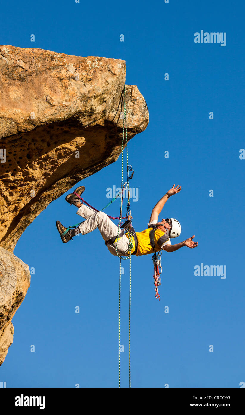 Climber free rappels from the summit after a challenging ascent. - Stock Image