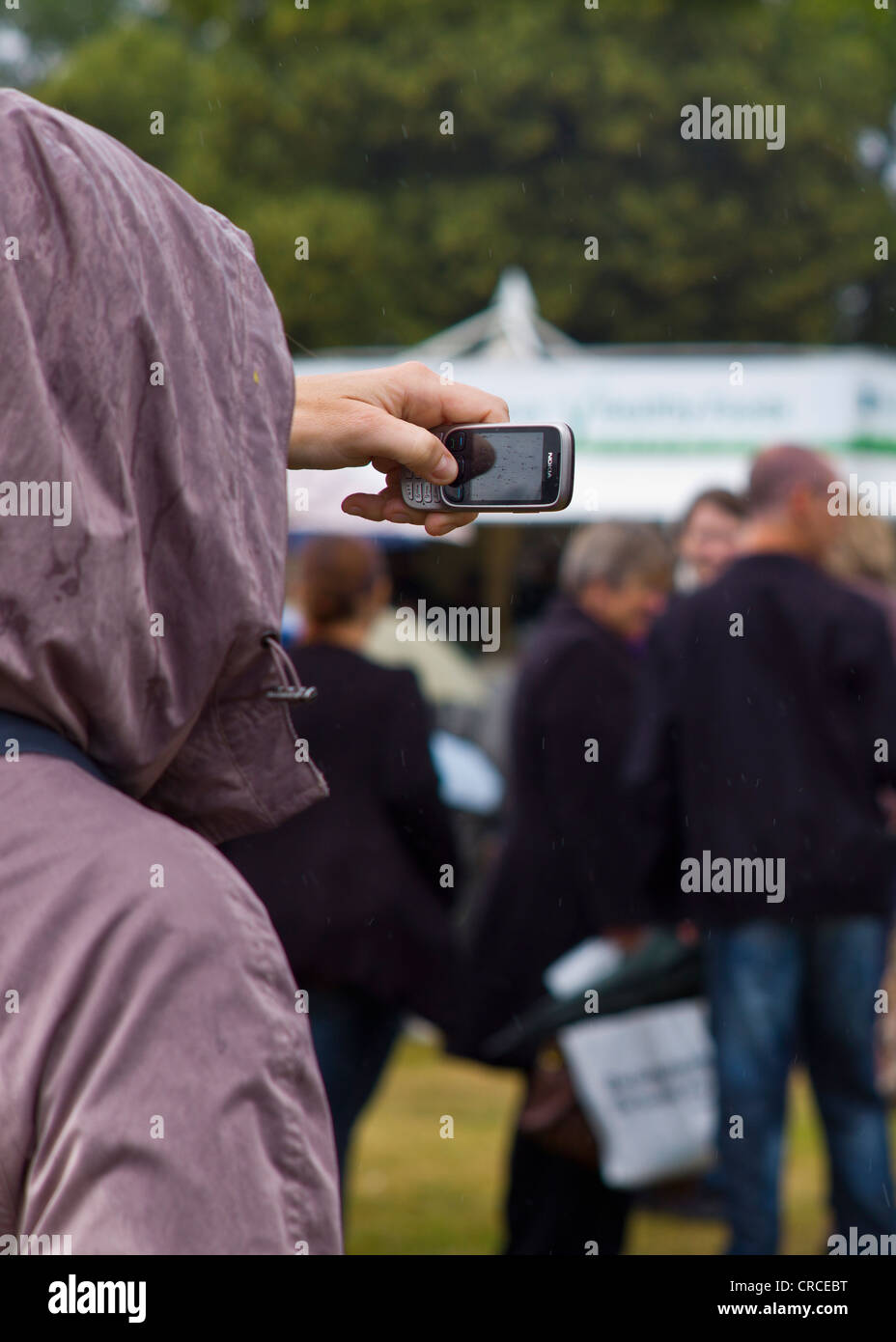 Taking a picture in the rain with a mobile phone - Stock Image