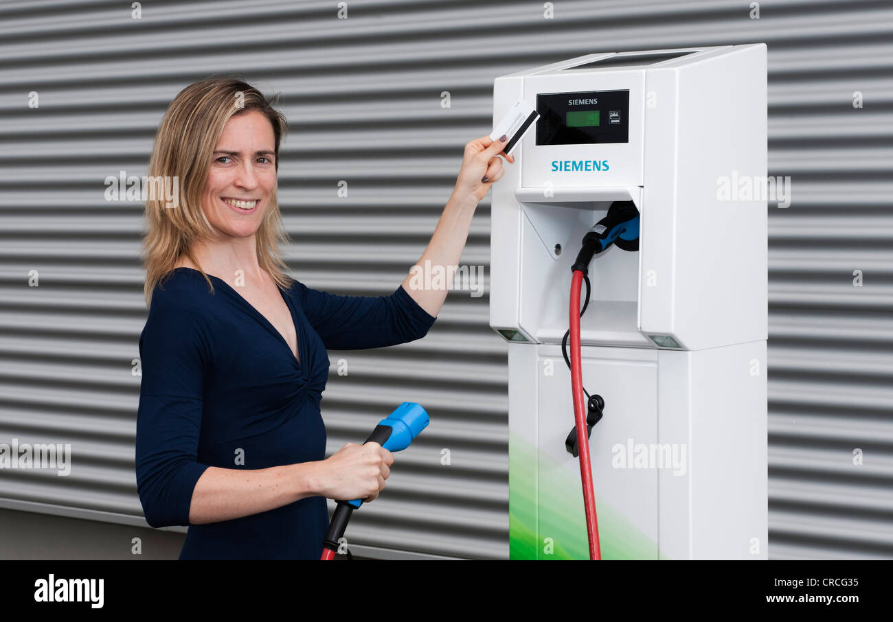 Woman holding a code card in front of the reader of a Charge CP700A charging station by Siemens, Fuerth, Bavaria - Stock Image