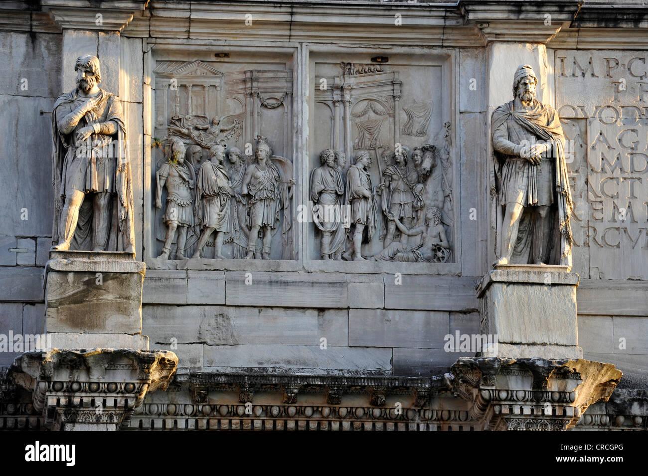 Statue of a Dacian prisoners and attic reliefs on the Arch of Constantine, Piazza del Colosseo, Rome, Lazio, Italy, - Stock Image