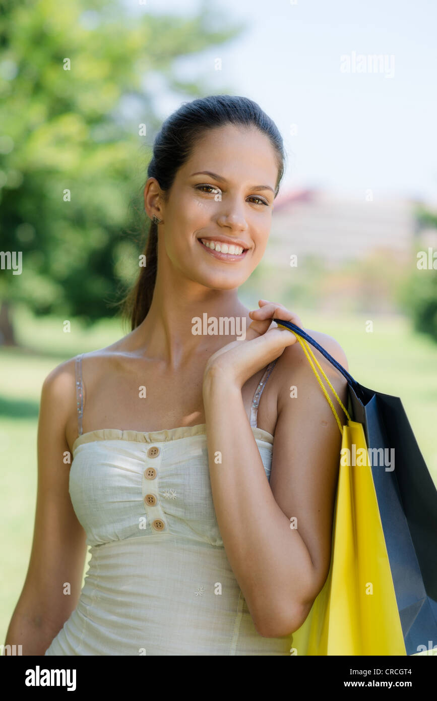 Consumerism, portrait of happy young woman smiling at camera with shopping bags - Stock Image