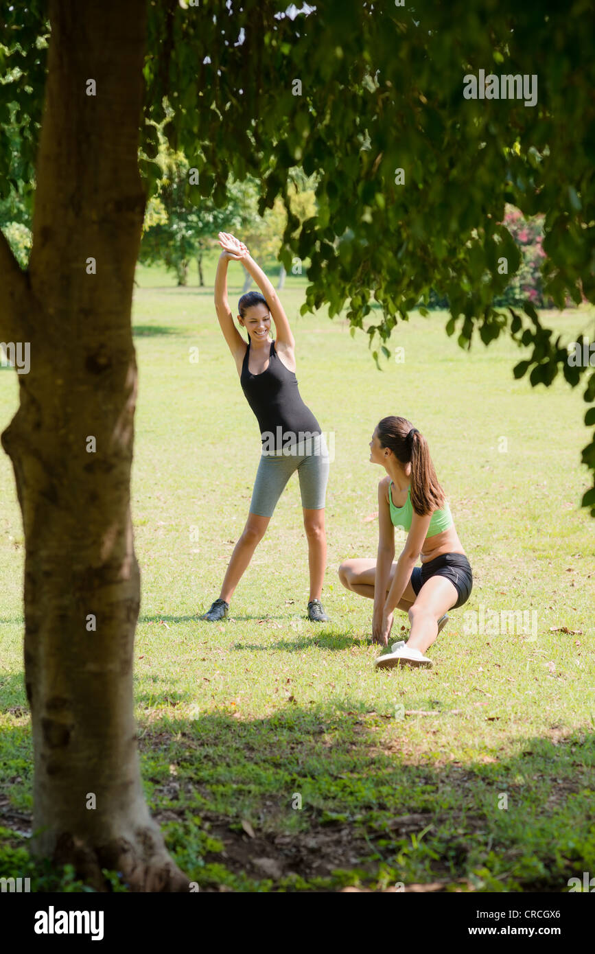 Two beautiful women stretching in city park after running and sport activity Stock Photo