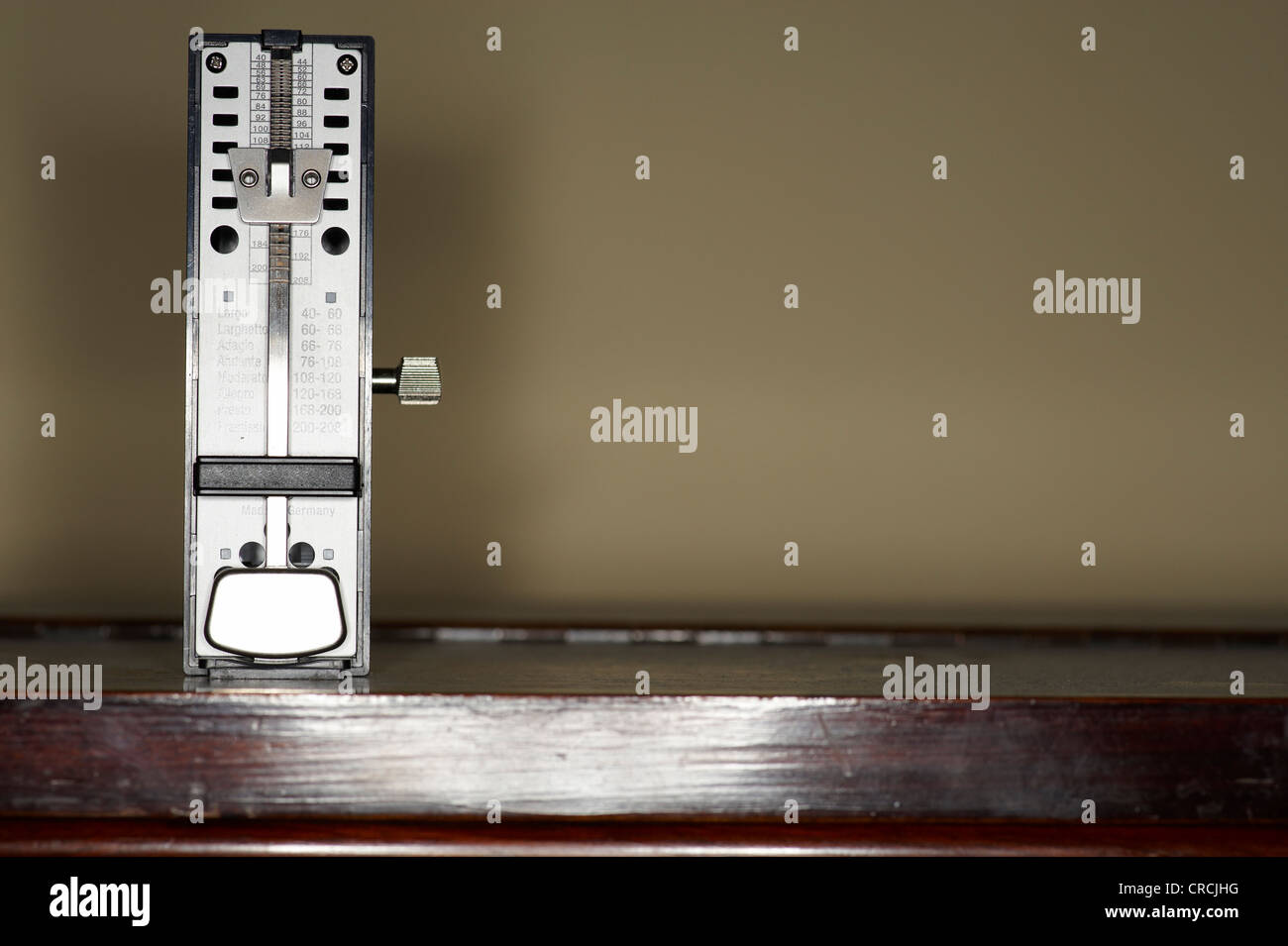 Metronome standing on a piano - Stock Image
