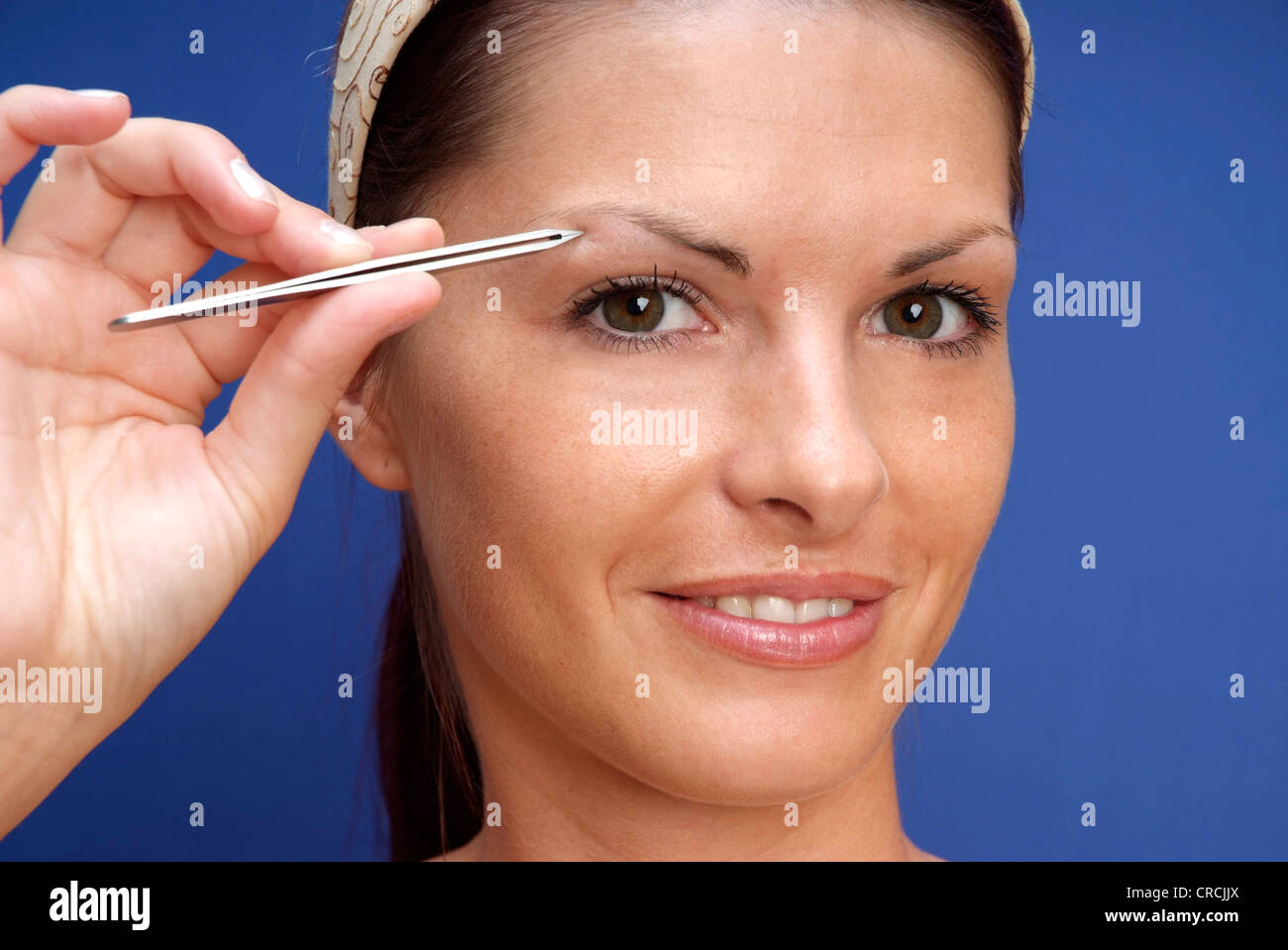 young cute woman plucking her brows - Stock Image