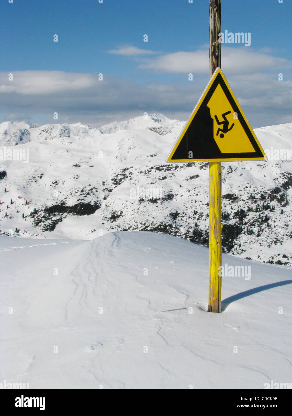Sign in snowy mountain scenery of a skiing area warning against danger of falling into deep precipice, Italy, Suedtirol, - Stock Image