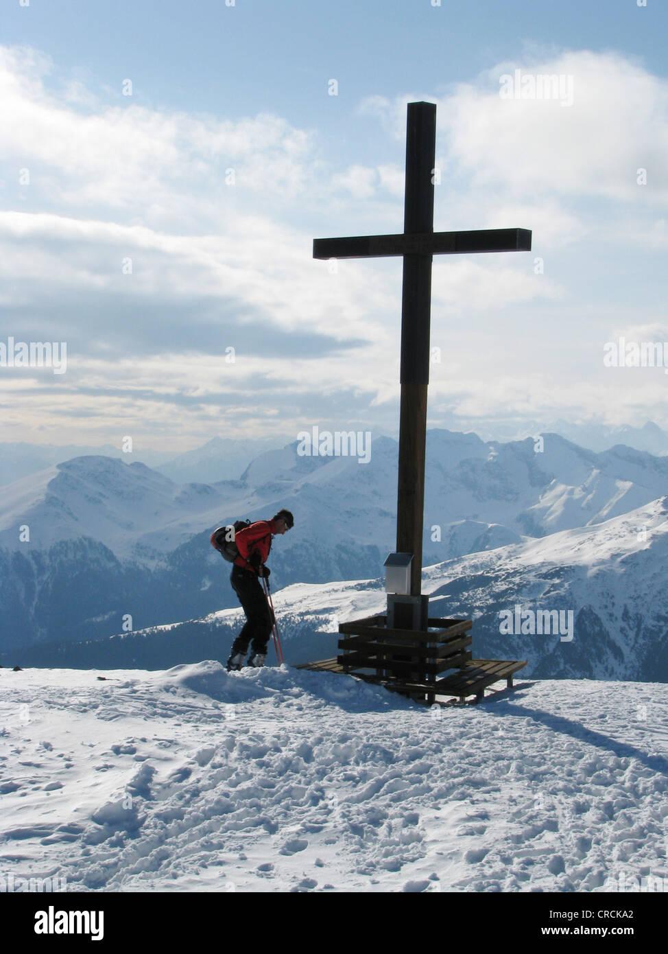 Cross on peak of mountain in snowy mountain scenery - mountain climber with touring ski has reached the mountain - Stock Image