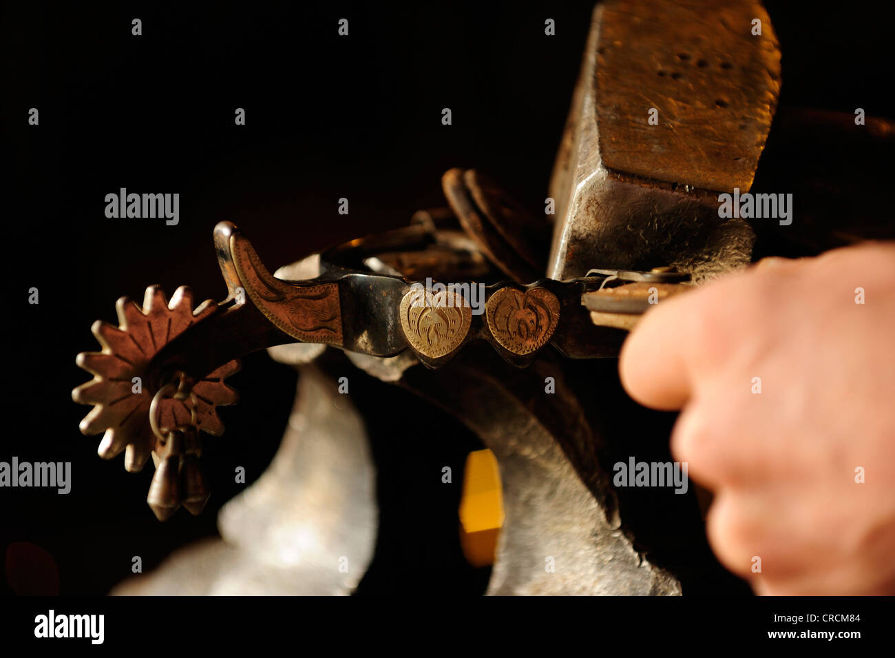 Spurs on cowboy boots being clamped in a vice and straightened with a hammer - Stock Image