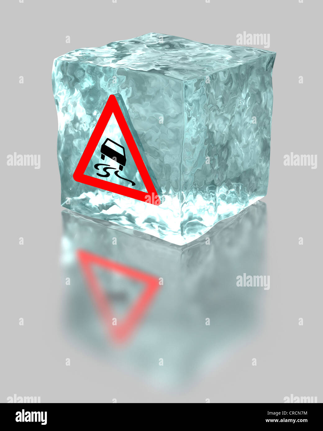 Block of ice with a traffic warning sign for slippery roads, symbolic image for the mandatory use of winter tyres - Stock Image