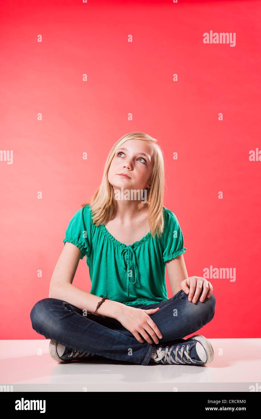 Pensive teenage girl looking up - Stock Image