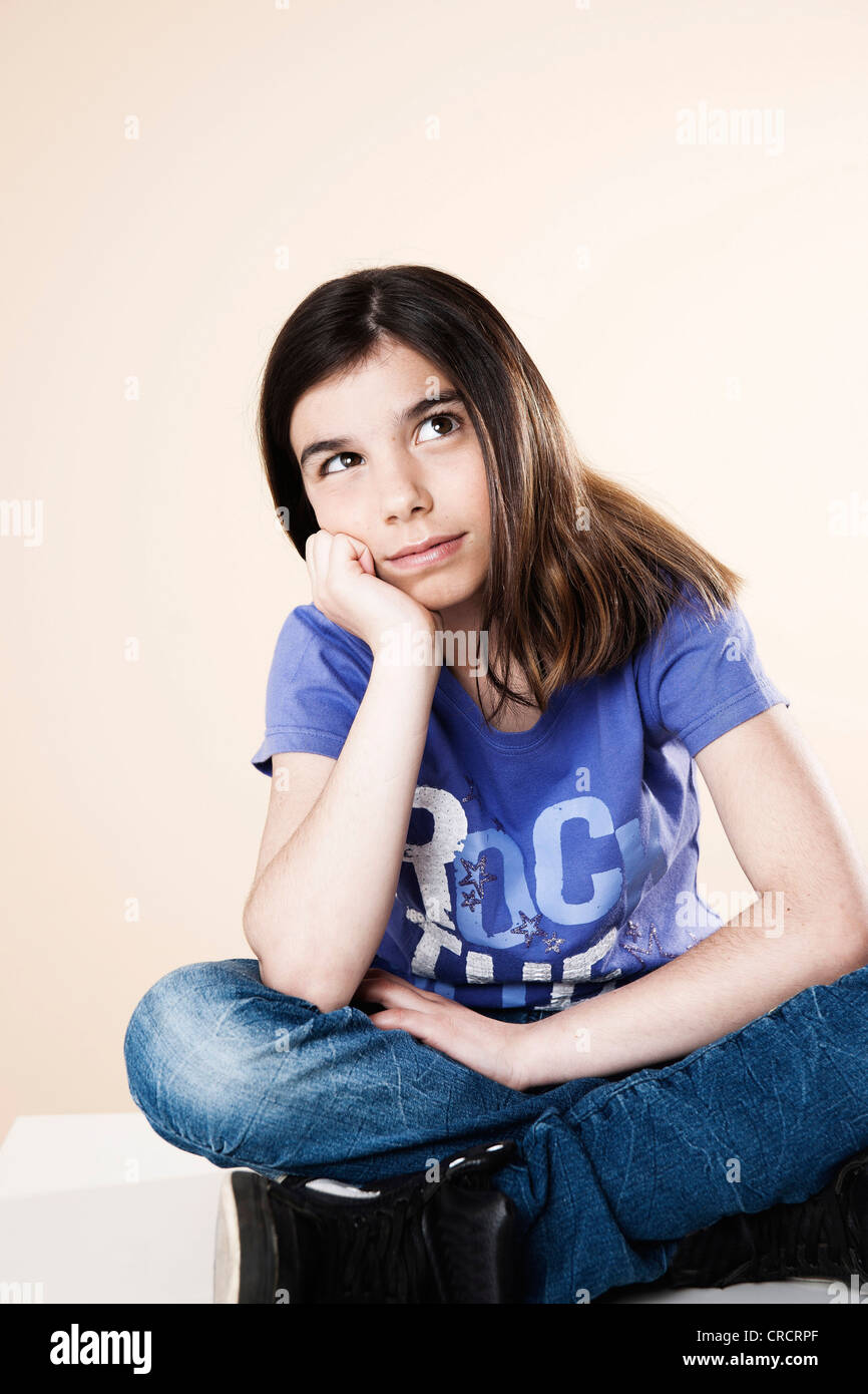 Girl sitting on table looking up - Stock Image