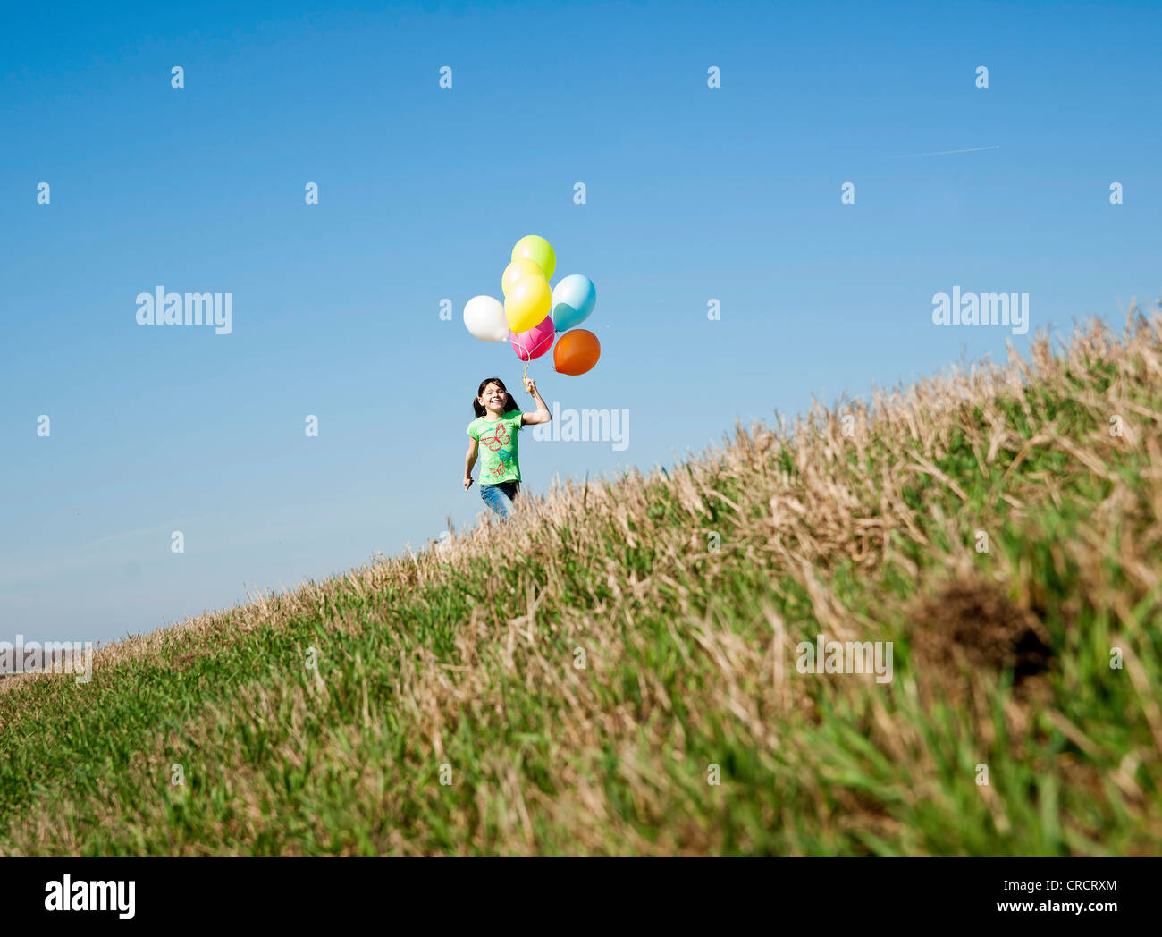 Girl running in meadow with balloons - Stock Image