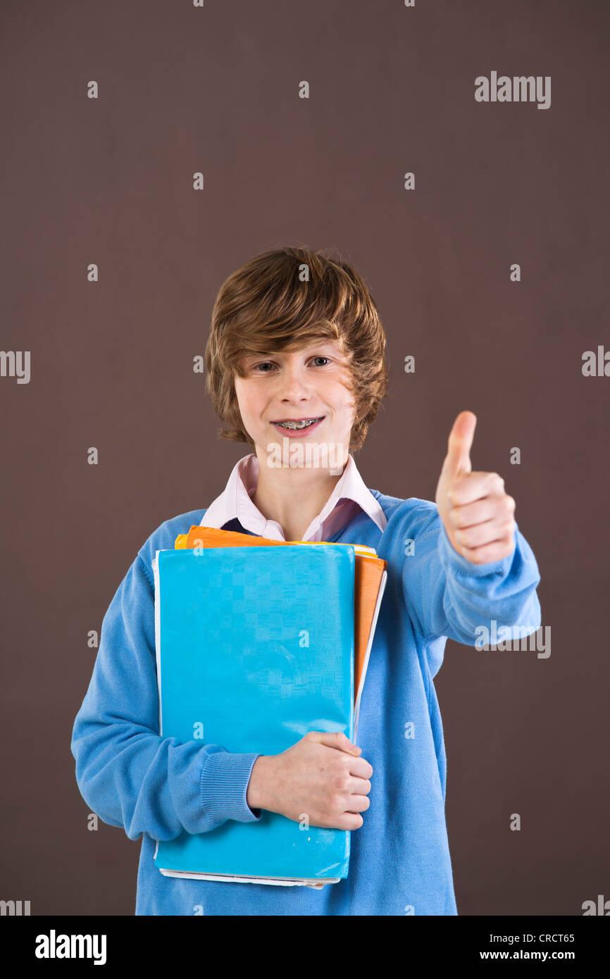 Optimistic teenage boy holding folders - Stock Image
