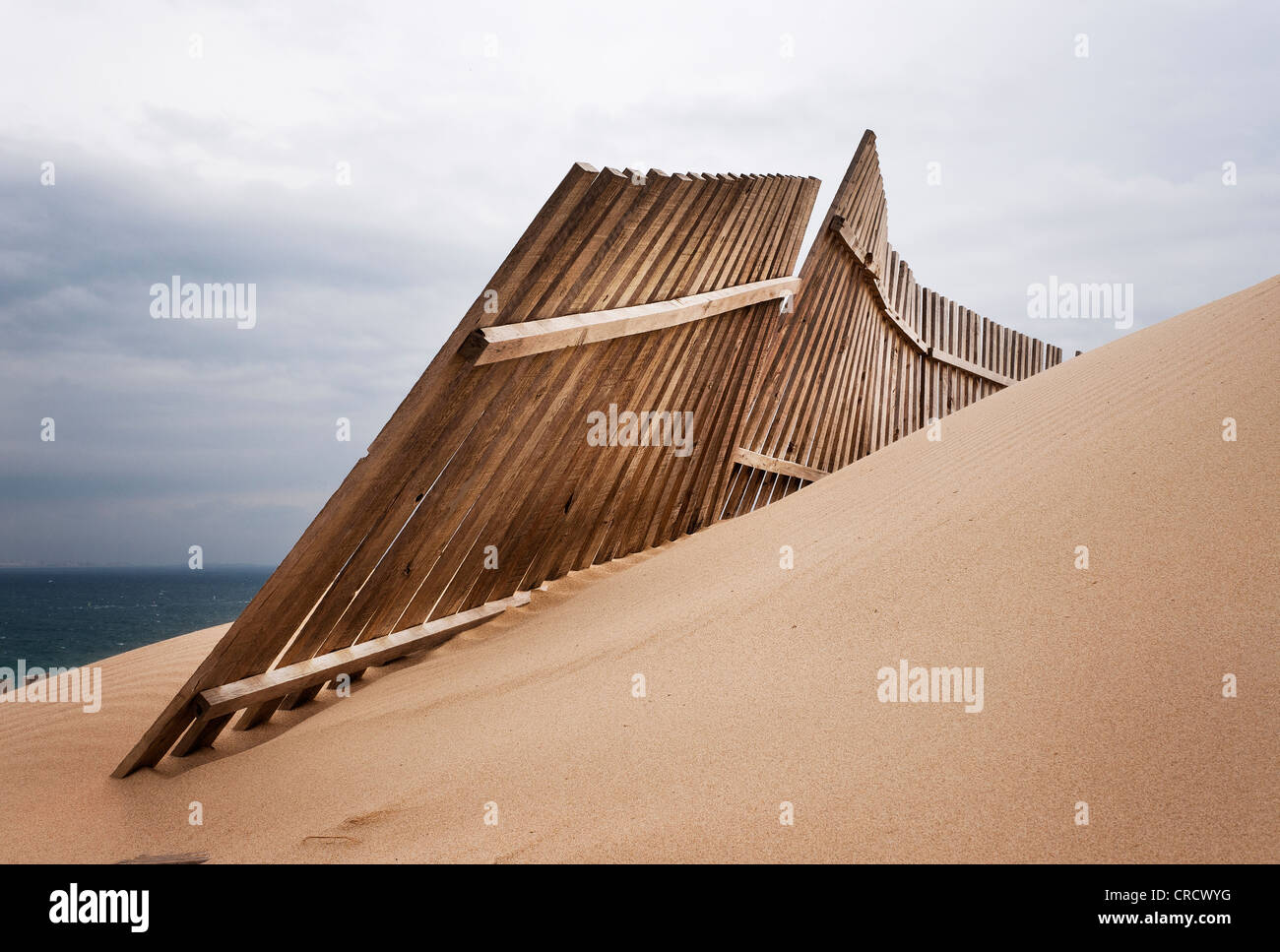 Wooden fence protecting the advance of sand dunes. - Stock Image