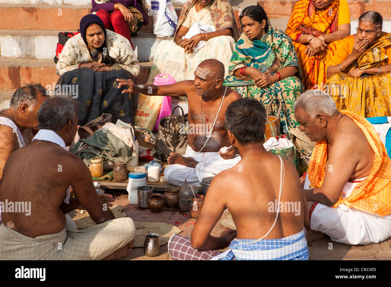 Hindu pilgrims listen holy word from Brahman on the Ghat in Varanasi, Uttar Pradesh, India - Stock Image
