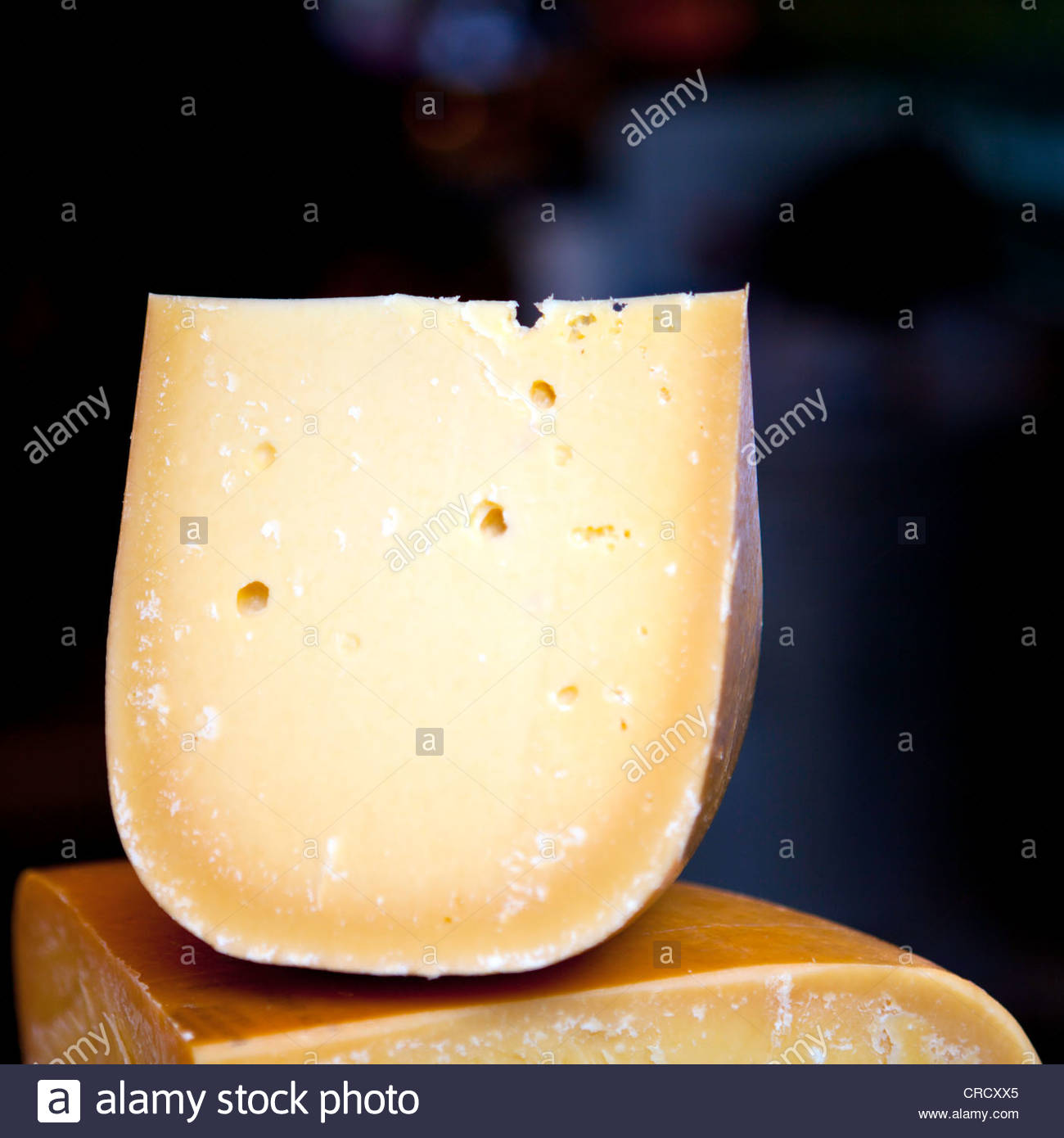 Artisan cheese wheel with smaller piece on top - Stock Image