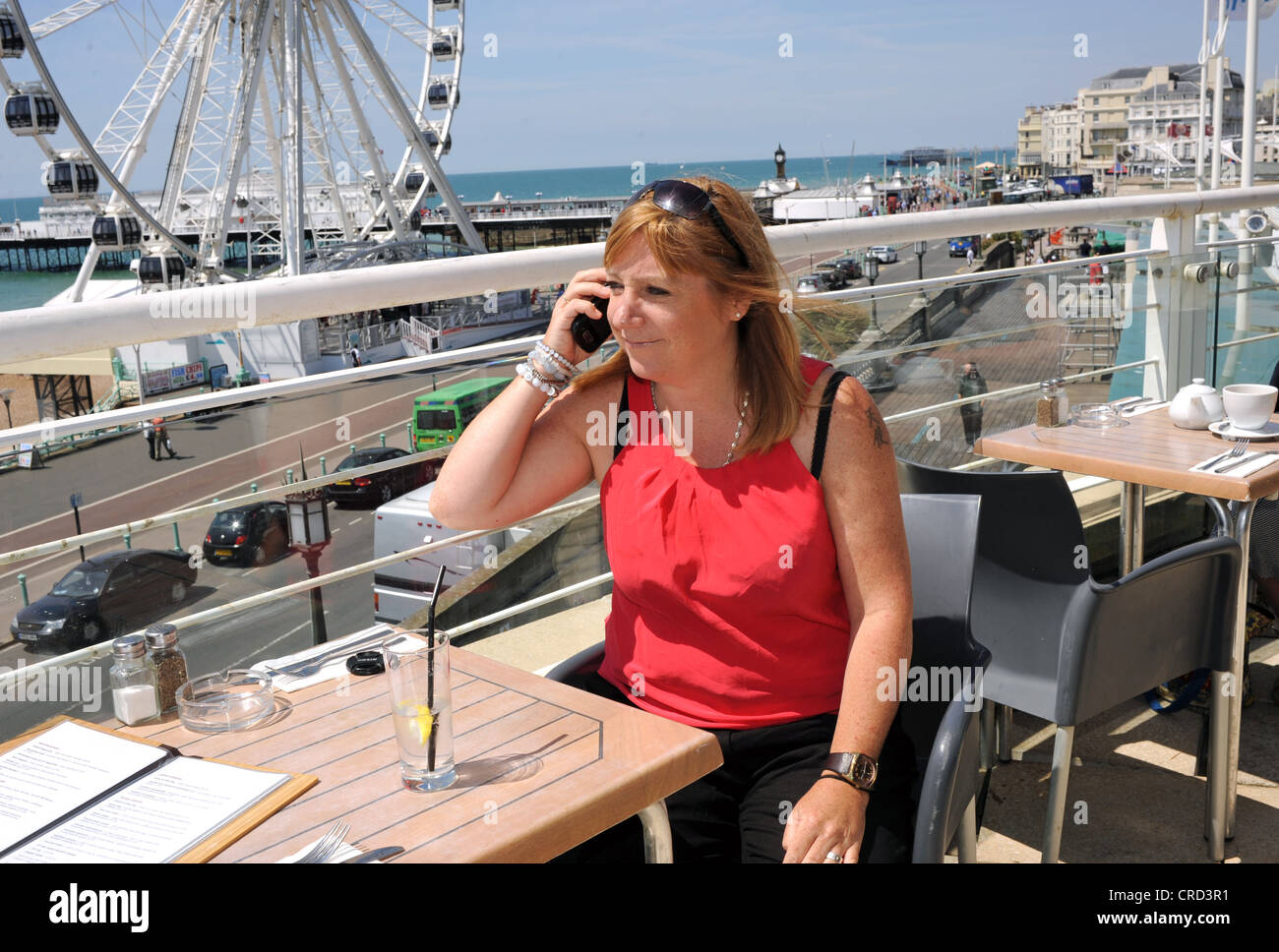 Woman enjoying a drink at seafront cafe bar near the Wheel of Excellence Sussex UK using mobile phone to make a - Stock Image