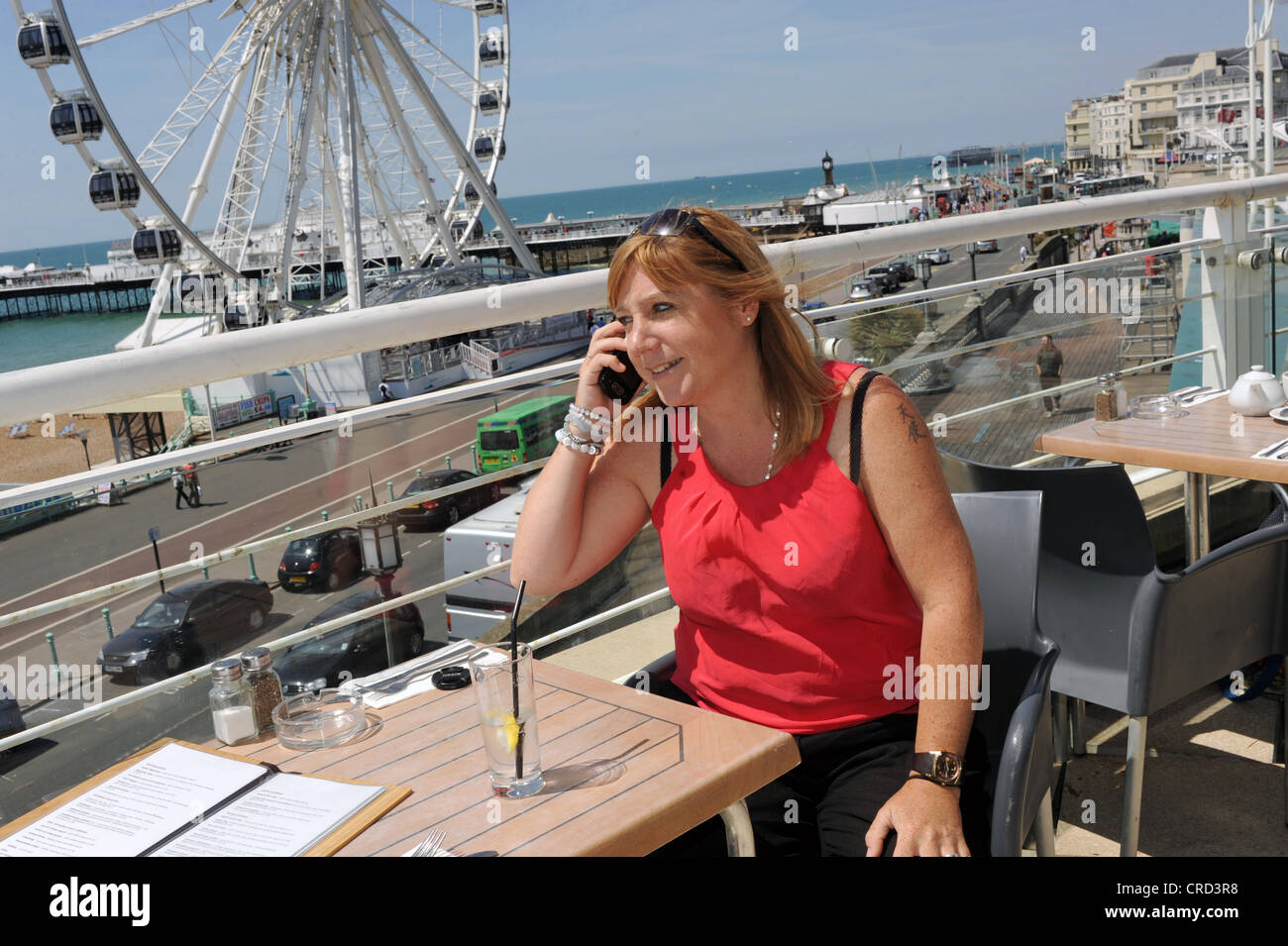 Woman enjoying a drink at seafront cafe bar near the Wheel of Excellence Sussex UK using mobile phone to make a Stock Photo