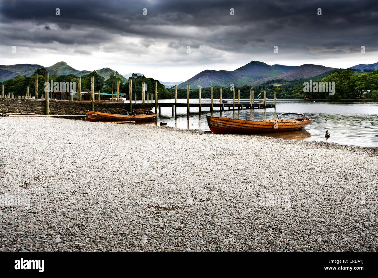 derwant water lake keswick rowing boat wooden cgi backgrounds car stone shingle banking jetty mountains - Stock Image