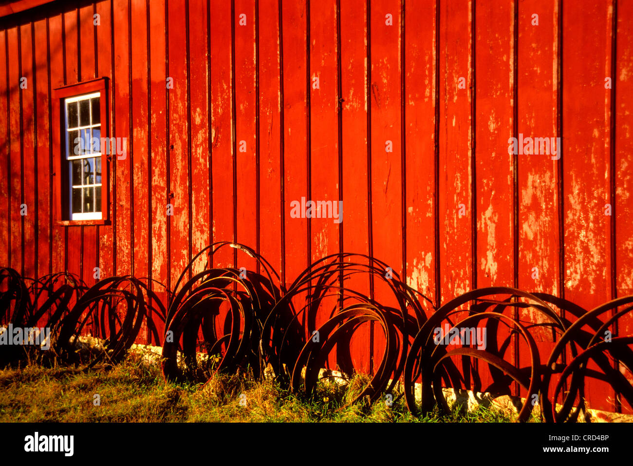 Wagon Wheel iron tires line the side of the wheelwrights shop at Old World Wisconsin in Waukesha County, USA, Wisconsin - Stock Image