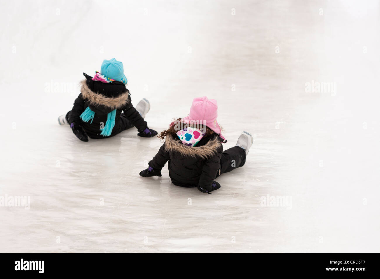 Two girls slide down an ice slide. At the Snowflake Kingdom at Winterlude - Stock Image