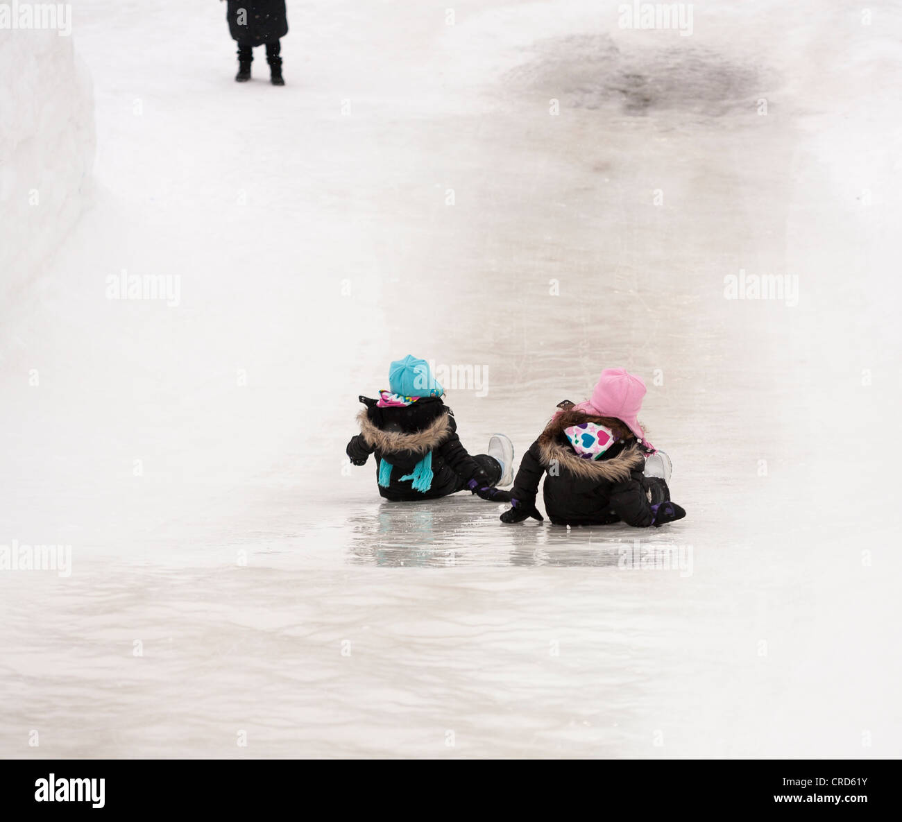 Mother's Waiting: two girls slide down an ice slide.  Part of the facilities at the Snowflake Kingdom at Winterlude. - Stock Image