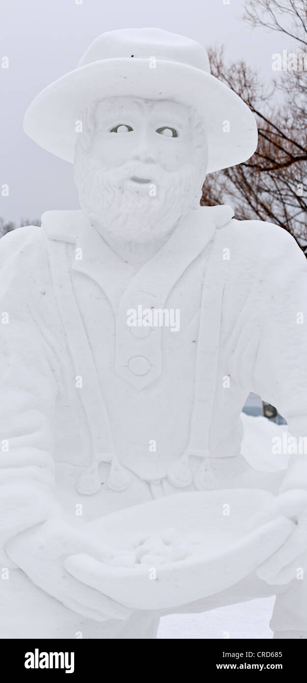Snow Sculpture of a Klondike gold prospector.  A larger than life creation at the Snowflake Kingdom at Winterlude - Stock Image