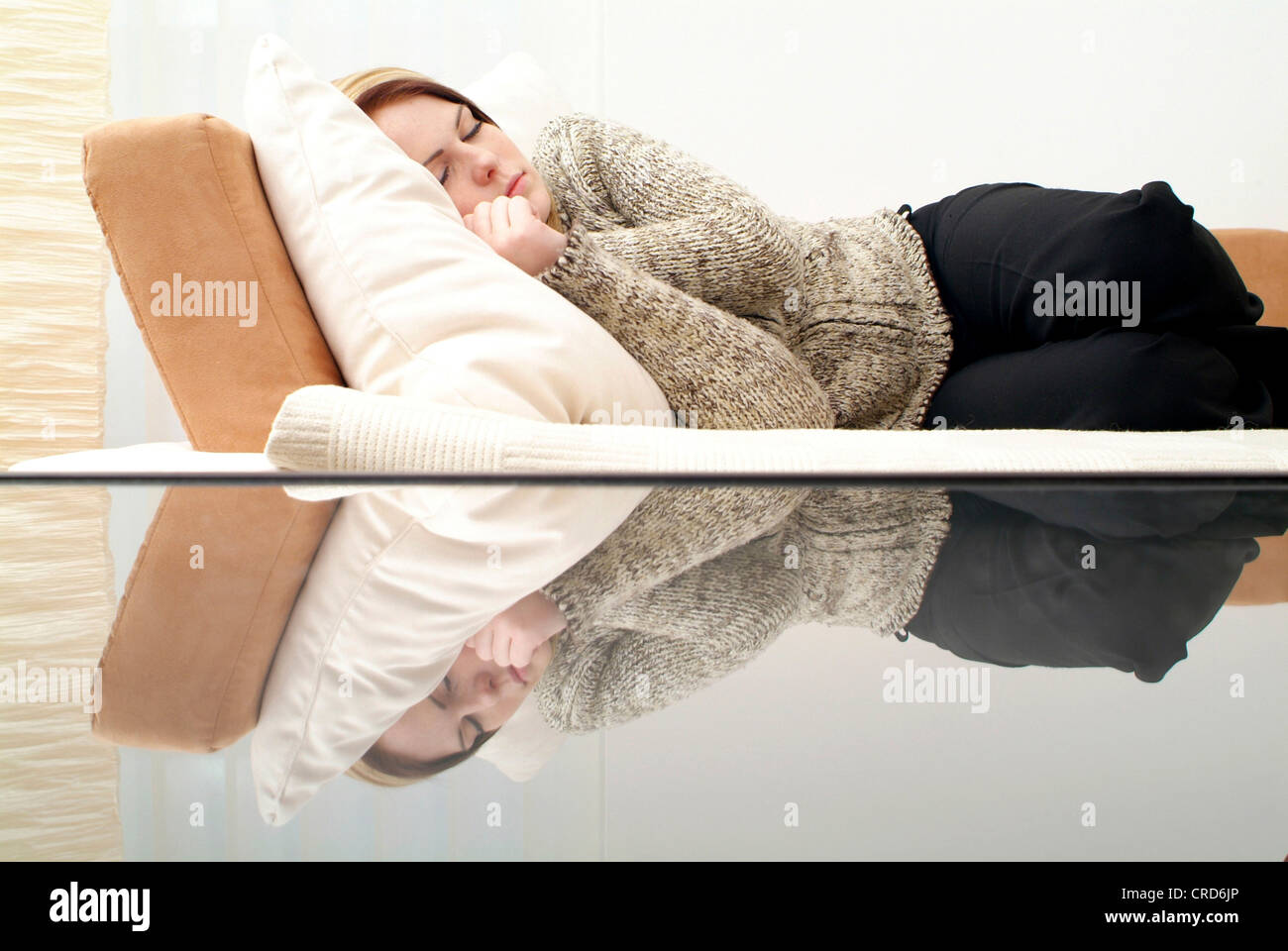 young woman sleeping on couch - Stock Image