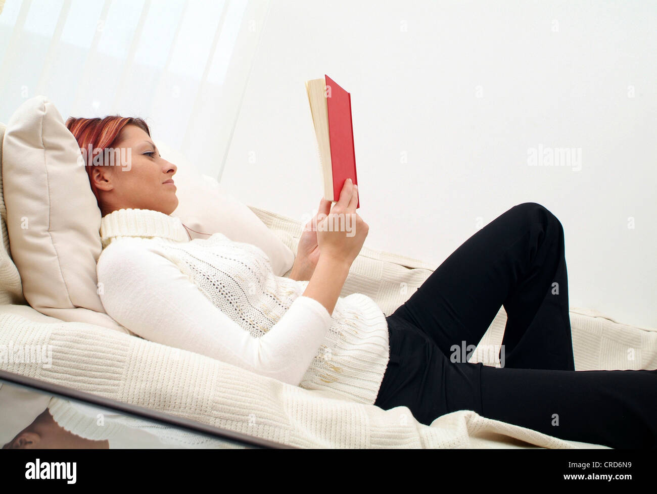 young woman on couch, reading a book - Stock Image