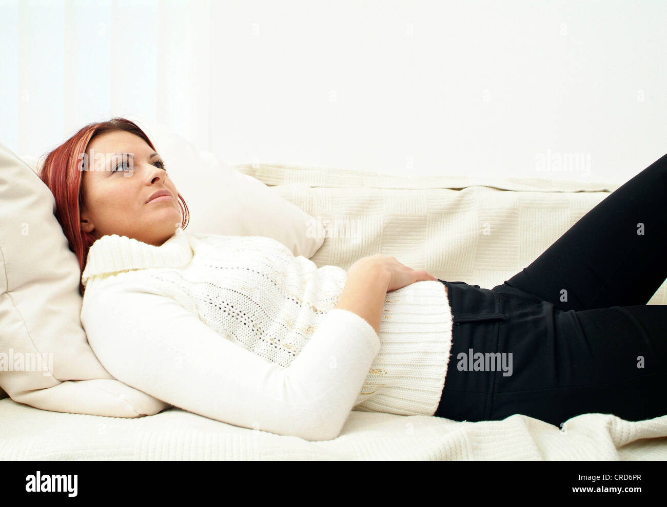 thoughtful young woman lying on a couch - Stock Image