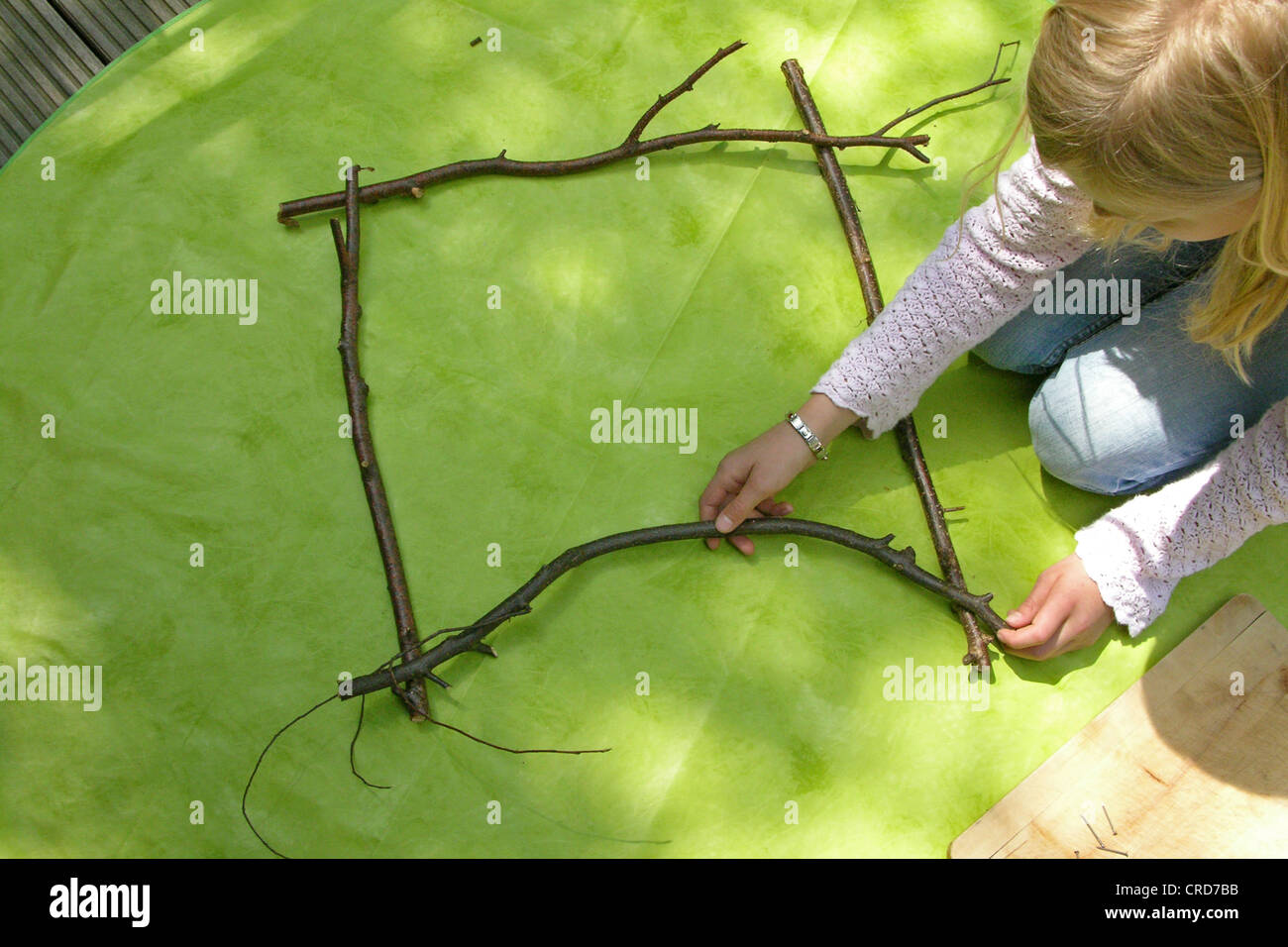 little girl building a picture frame with twigs, series picture 1/7 - Stock Image