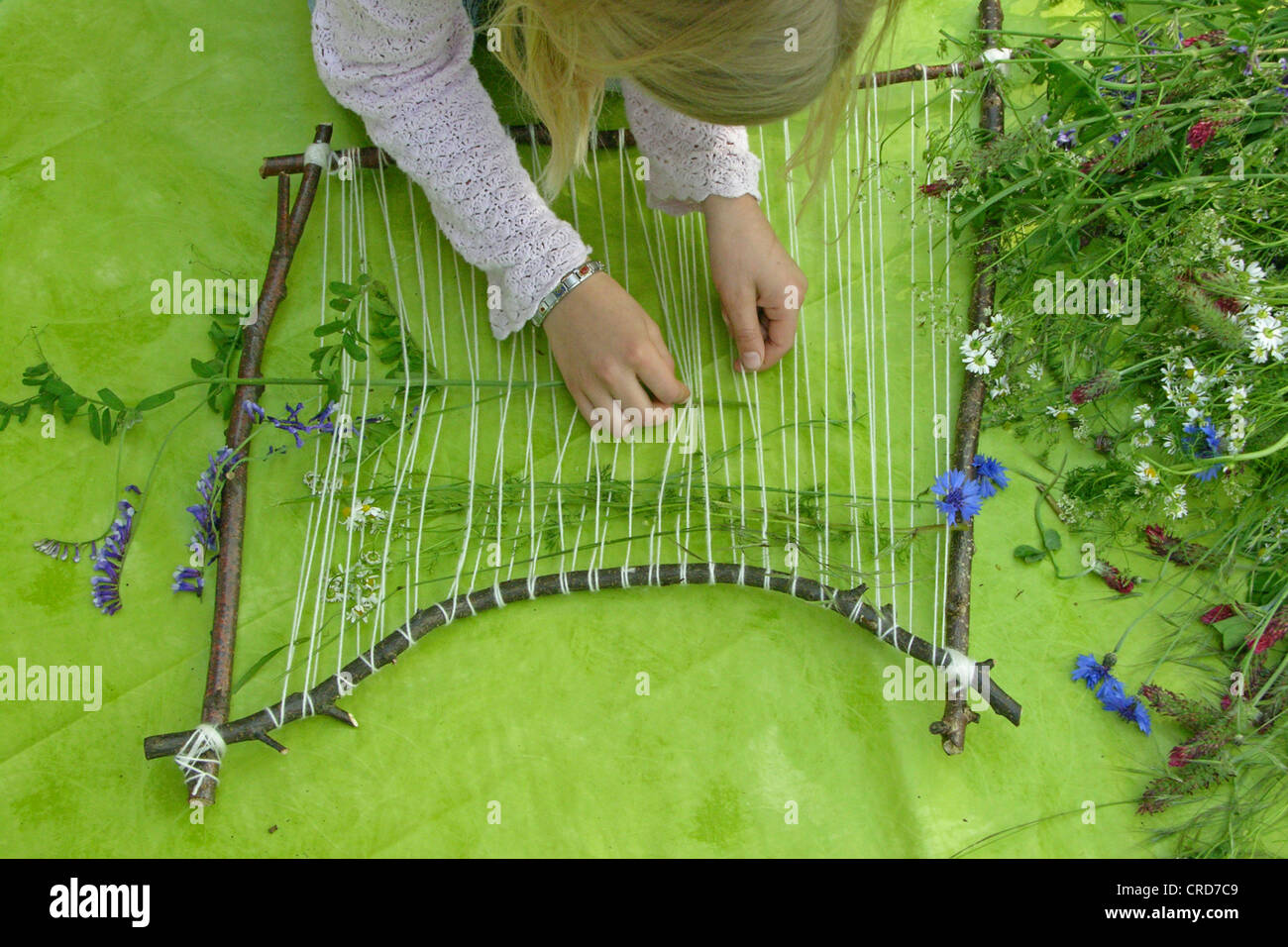 little girl building a picture frame with twigs and flowers, series picture 5/7 Stock Photo