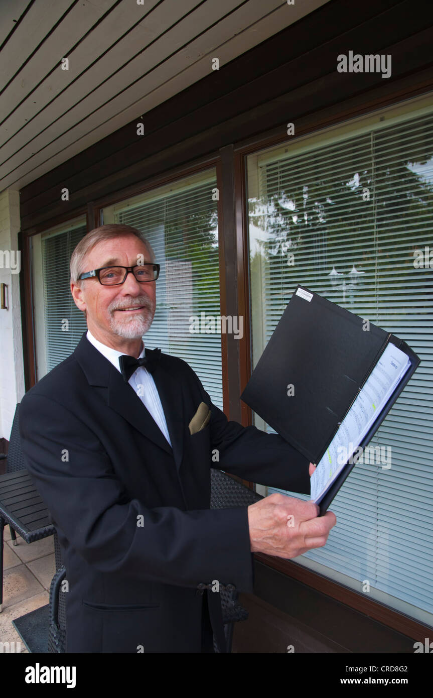 Man in his early 70s practising for choir singing with notes Finland Europe - Stock Image
