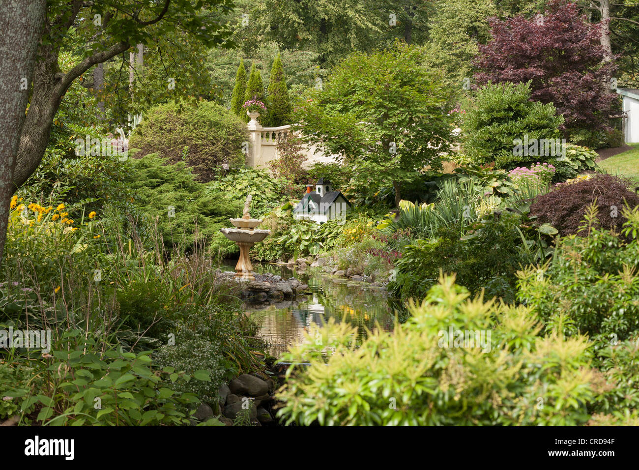 Lush Spring vegetation at the Halifax Public Gardens. A fountain and a mini house feature - Stock Image