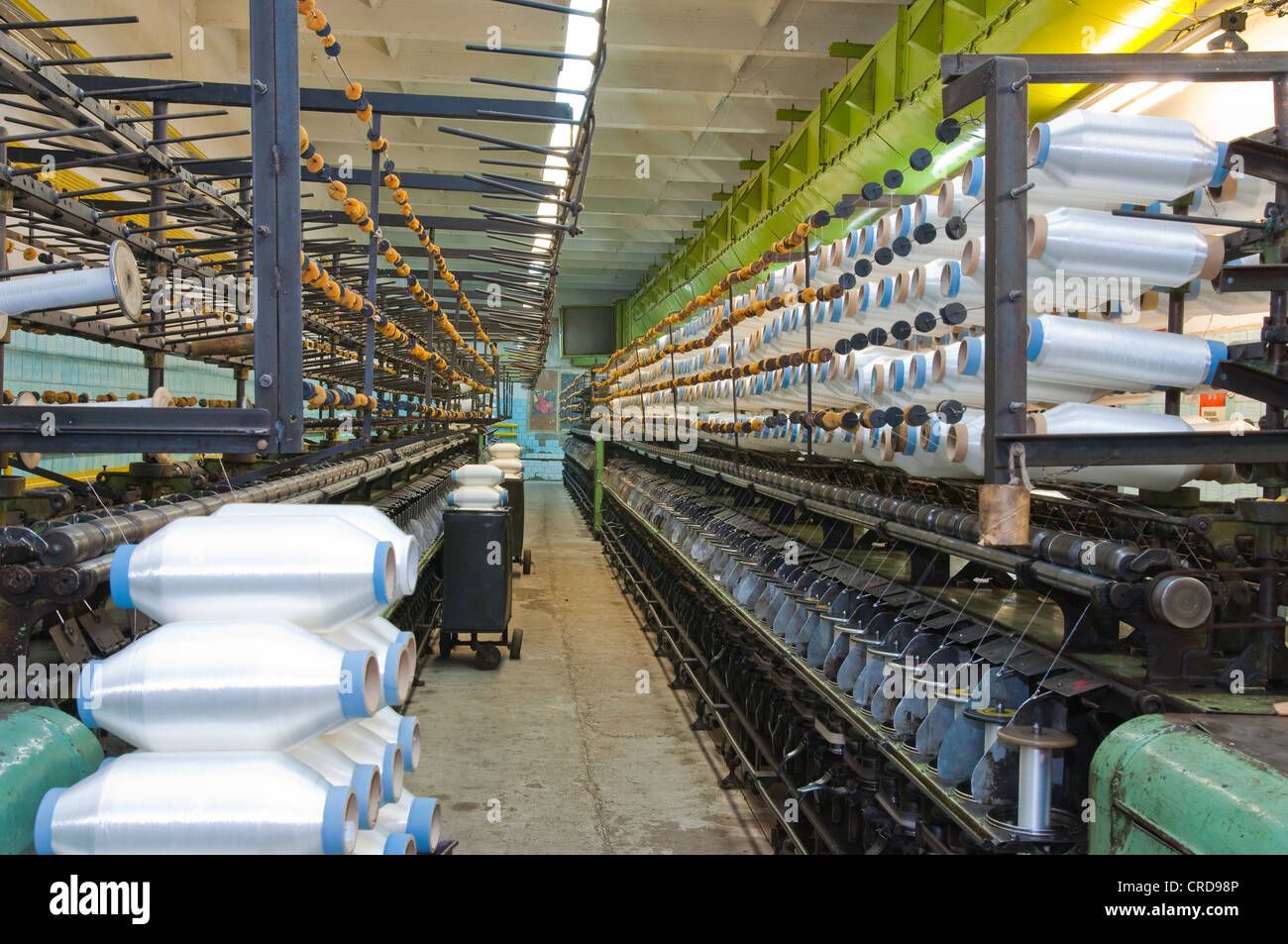 Textile factory equipment in the workshop and thread on large spools - Stock Image