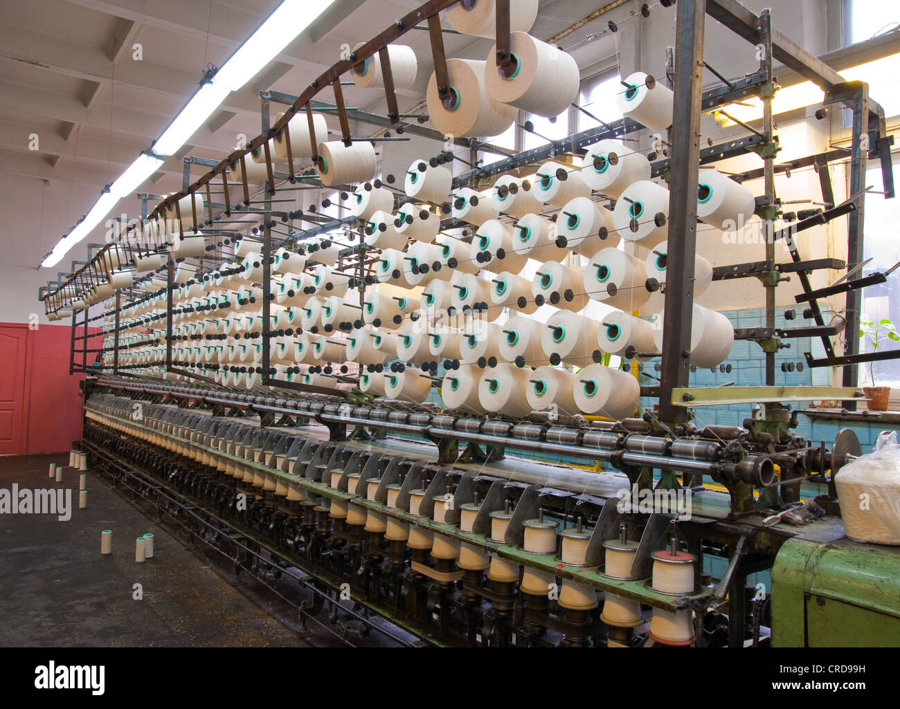 Cotton yarn on large spools and textile factory equipment in the workshop - Stock Image