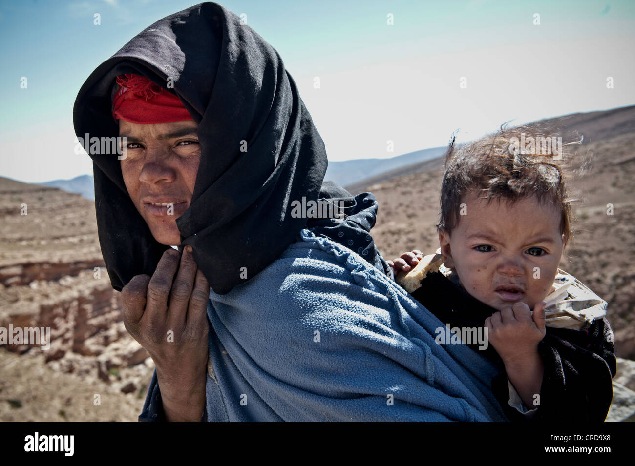 Nomad Berber mother carrying her baby Atlas Mountains, Morocco - Stock Image