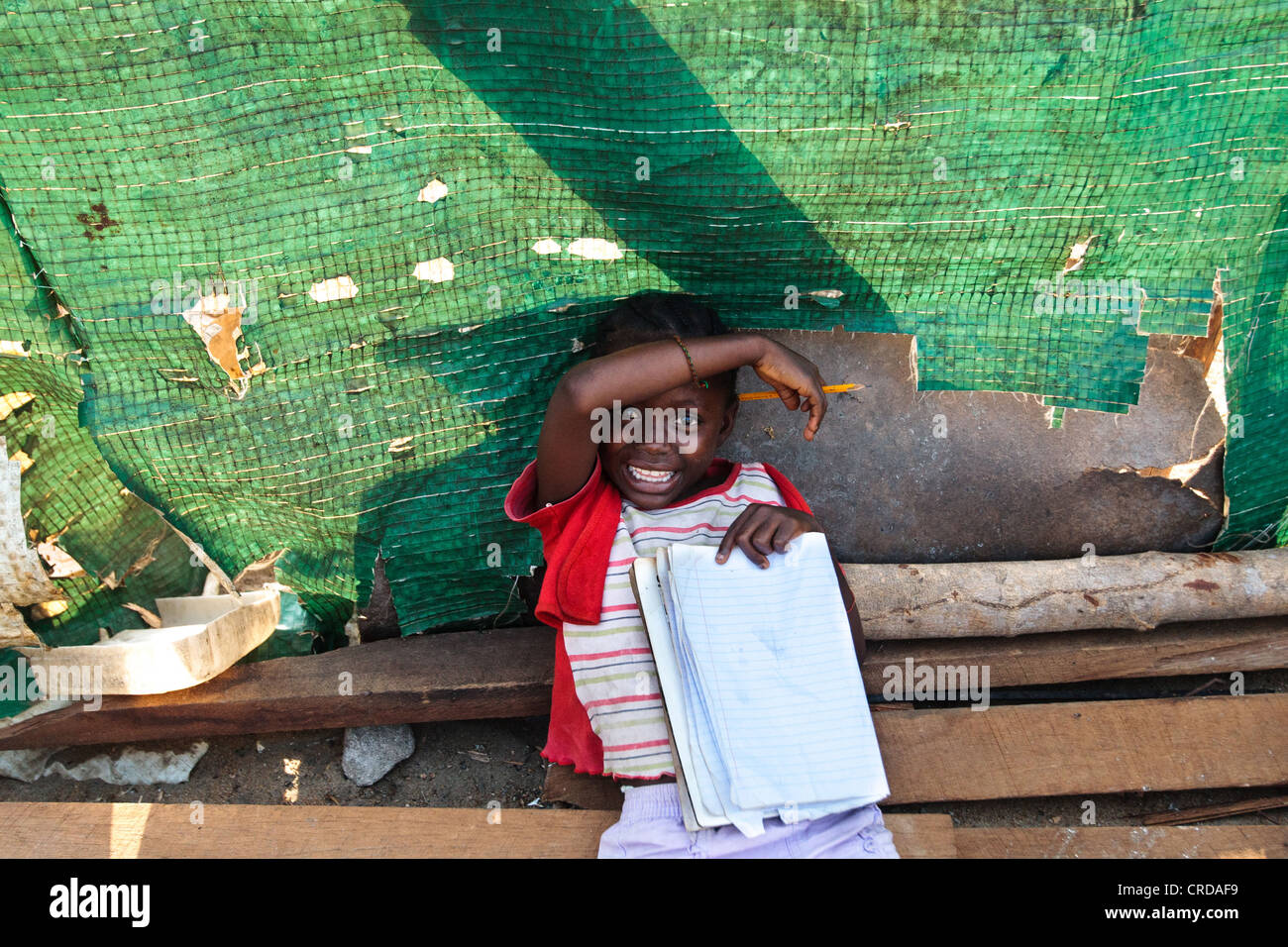 A girl laughs while doing her homework in the West Point slum of Monrovia, Montserrado county, Liberia on Monday - Stock Image