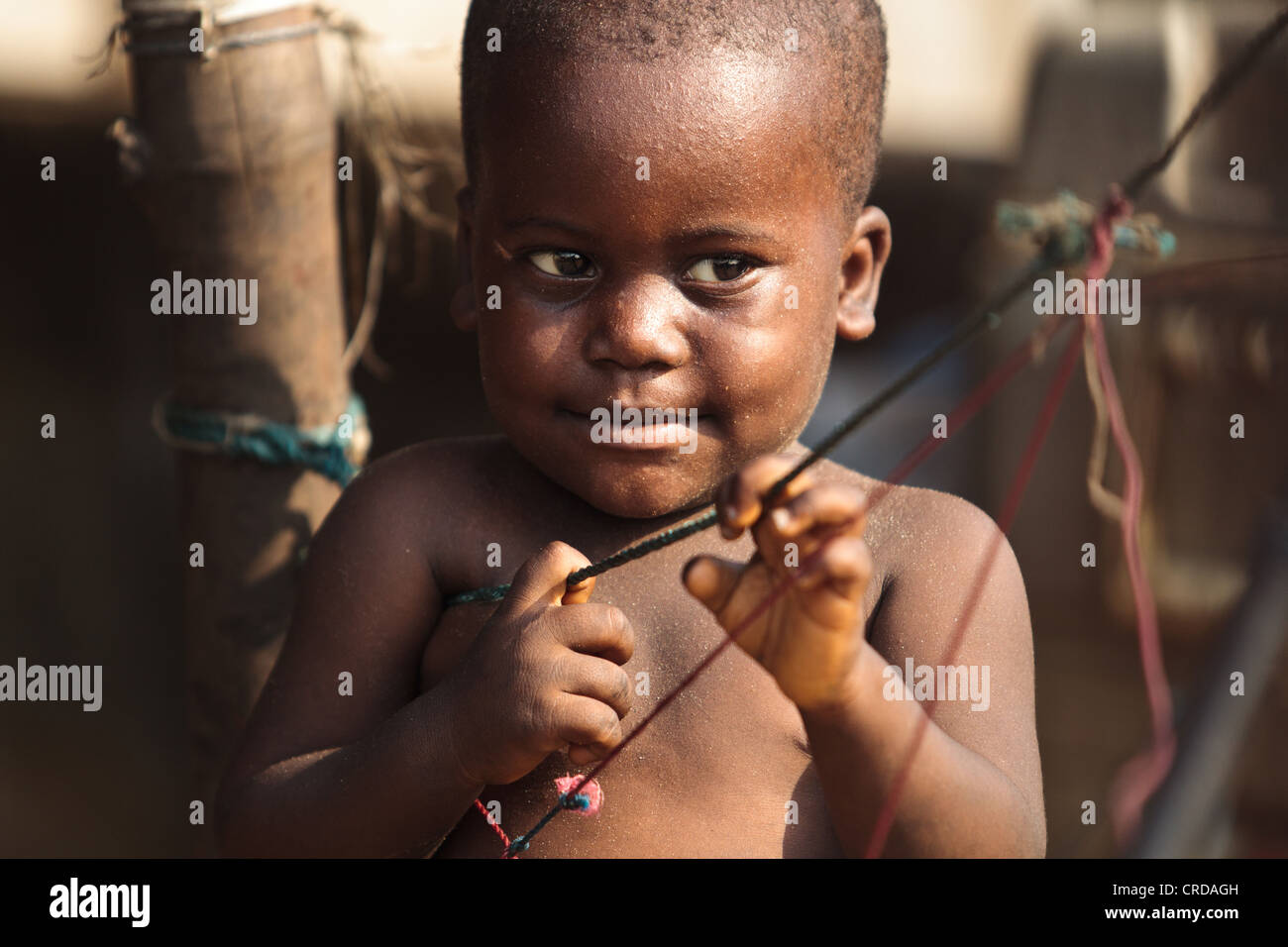 A boy plays with strings in the West Point slum of Monrovia, Montserrado county, Liberia on Monday April 2, 2012. - Stock Image