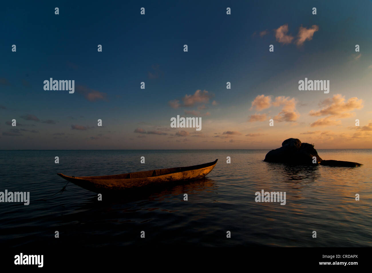 Traditional Malagasy boat near the beach at sunset, Madagascar, Africa - Stock Image