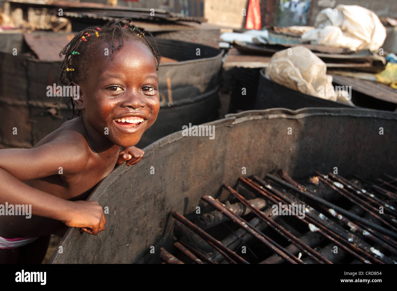 A girl stands next to a large barrel used to smoke fish in the West Point slum of Monrovia, Montserrado county, - Stock Image