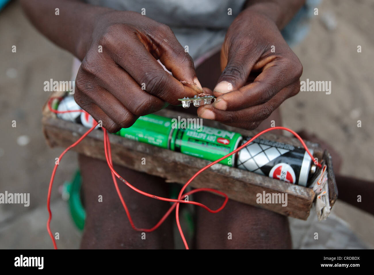 A boy plays with batteries and a small light in the West Point slum in Monrovia, Montserrado county, Liberia - Stock Image