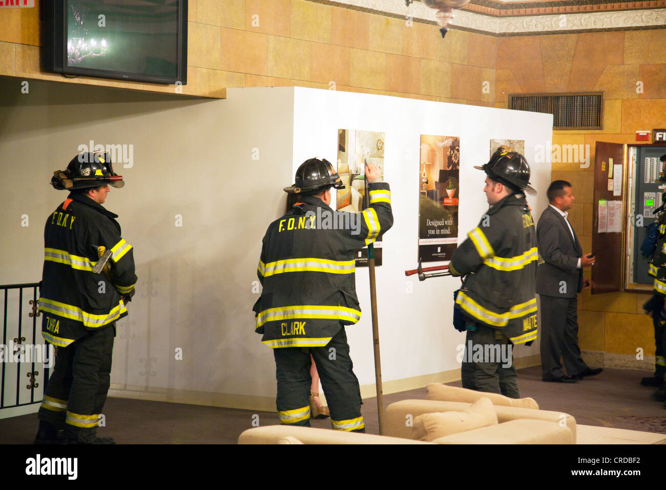 FDNY fire department New York City firemen stood around chatting in hotel building after emergency, fire brigade - Stock Image