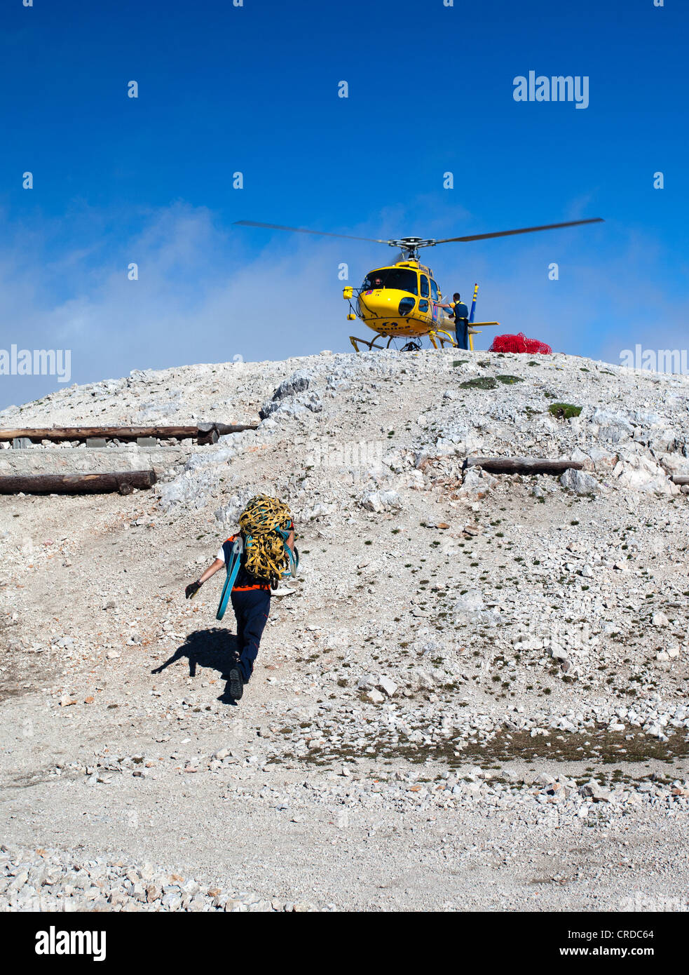 A helicopter drops off food and water supplies to Triglavski Dom mountain hut in the Julian Alps, Slovenia - Stock Image
