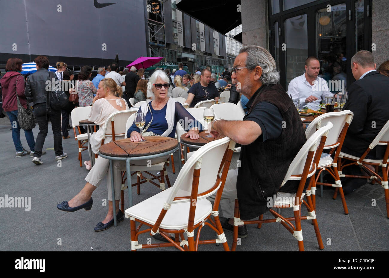 People enjoying the city atmosphere at Cafe Norden, a famous pavement and indoor restaurant and cafe on Strøget - Stock Image