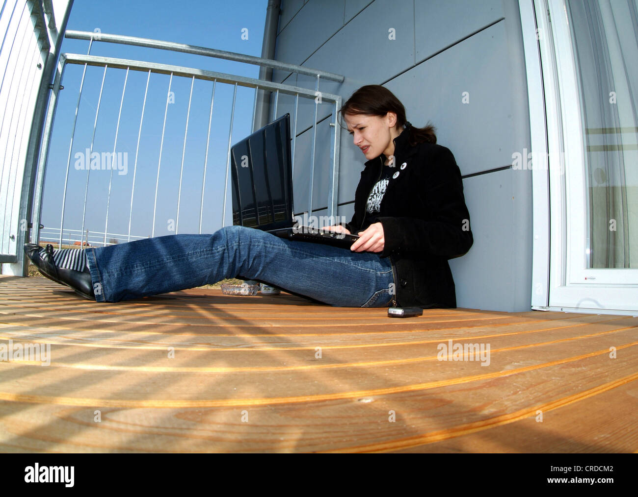 young woman sitting on sunny balcony, working with laptop - Stock Image