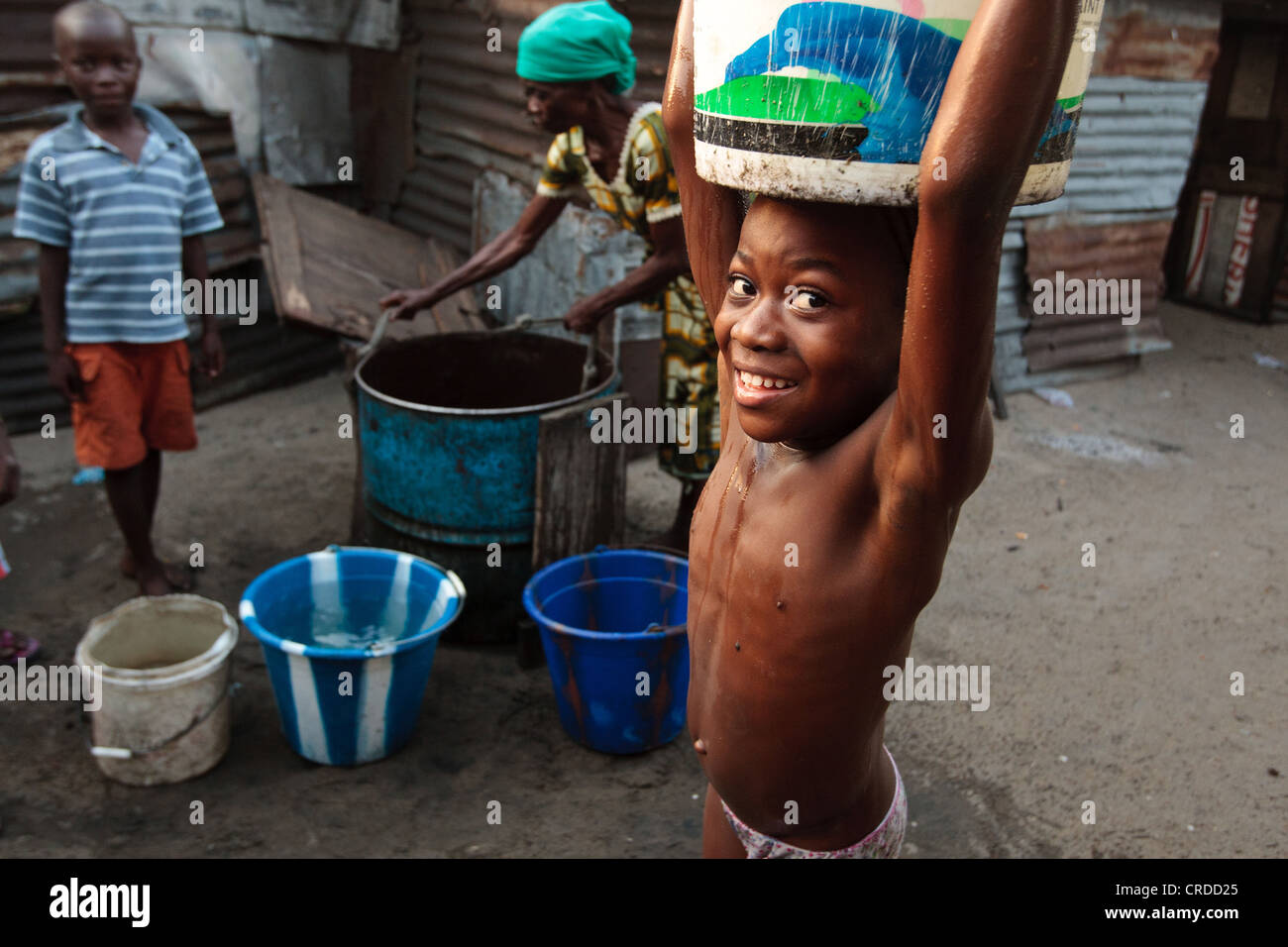 A girl carries a bucket of water she just filled from a well in the West Point slum in Monrovia, Montserrado county, Stock Photo