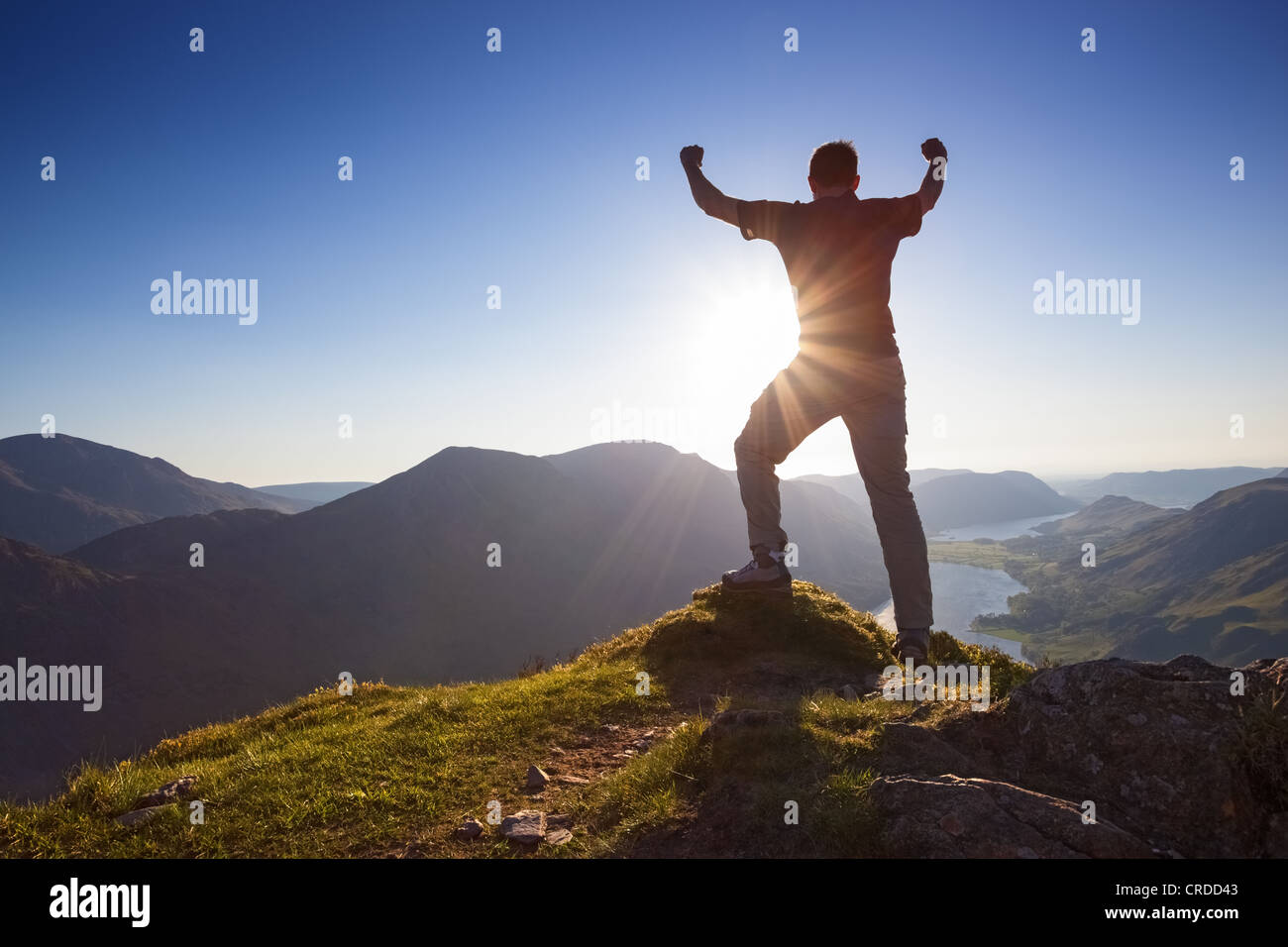 Man celebrating with his arms stretched in the air on the summit of a mountain. - Stock Image