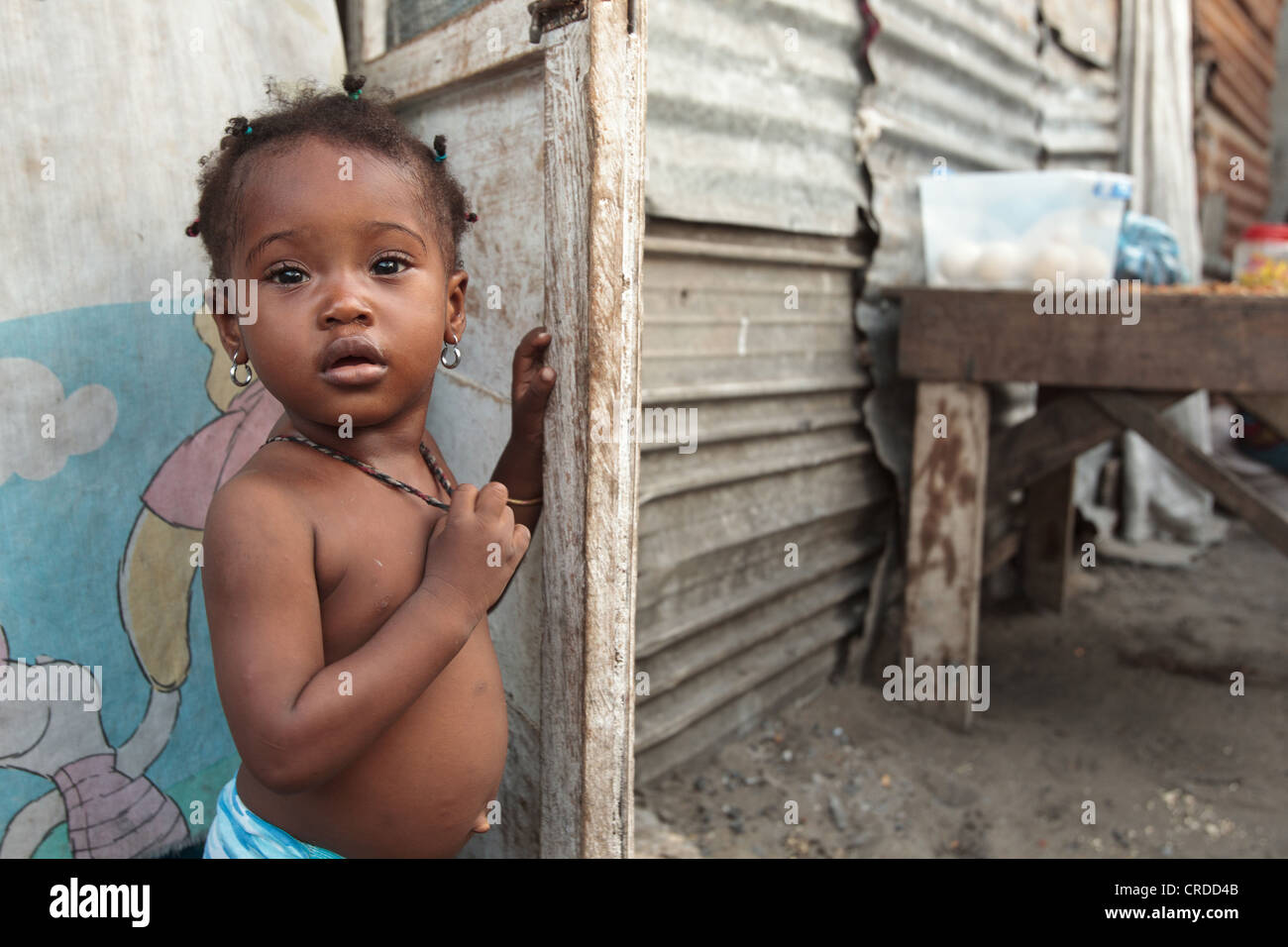 A young girl stands in the doorway of her home in the West Point slum in Monrovia, Montserrado county, Liberia - Stock Image